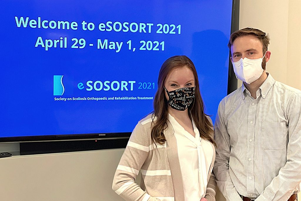 Christen and Kristian standing by TV with SOSORT Meeting Logo