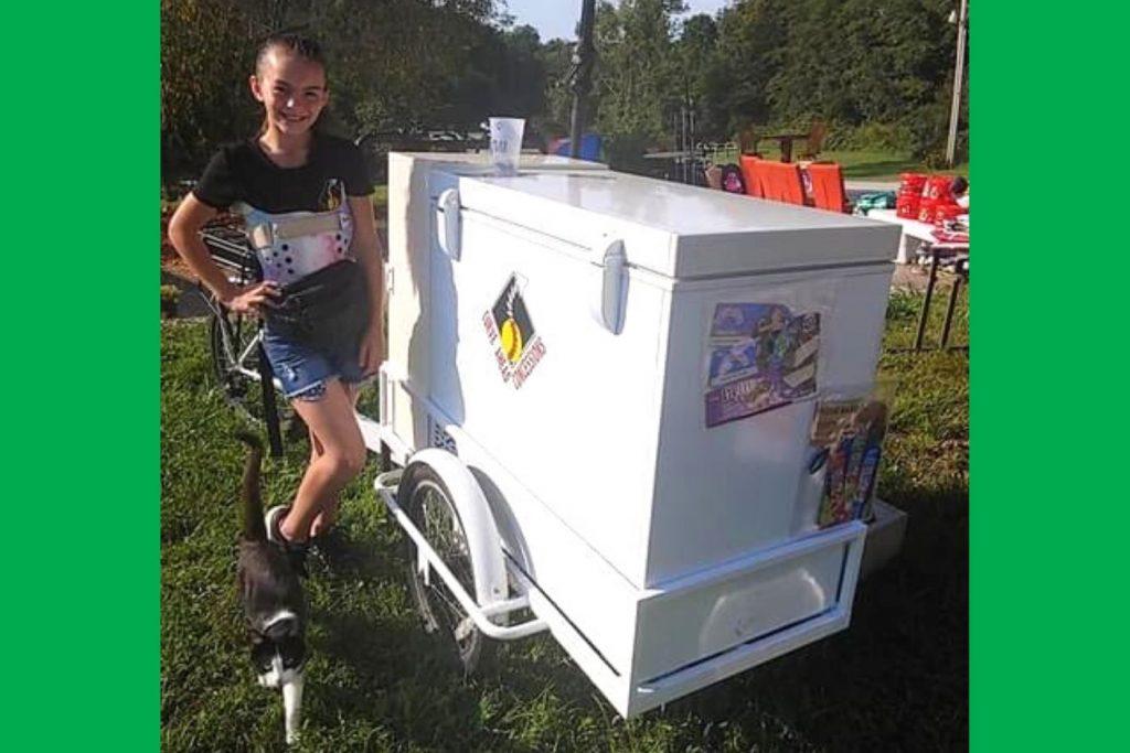 Nia wearing brace and standing next to ice cream cart